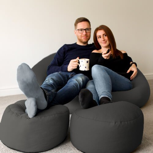 Couple sitting on Goliath Bean bag using matching footstools