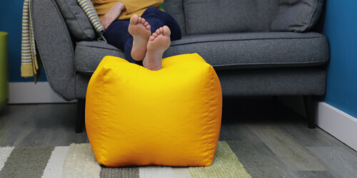 Outdoor bean cube being used indoors as a footrest