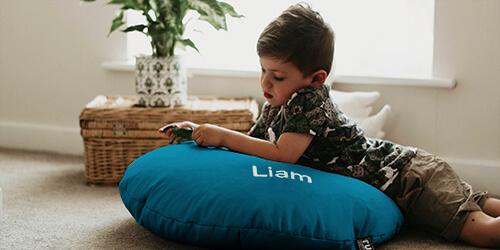 Little boy on personlaised smarty floor cushion